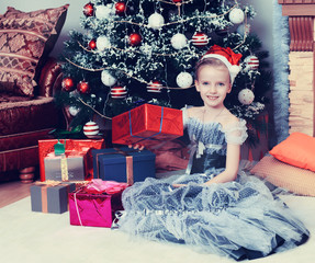 Little girl sitting near Christmas tree with a big gift.