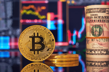 Golden bitcoin are stacked on a bright background of business graphs close-up. Bitcoin cryptocurrency