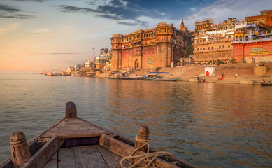 Ganges river boat ride at sunset overlooking the ancient Varanasi city, India.