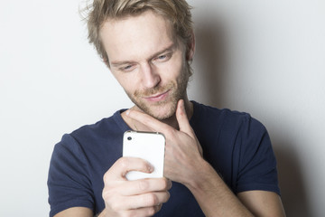 Handsome man looking at his smartphone with interested expression