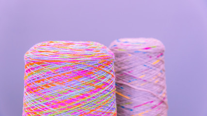 Reels or spools of multicolored sewing threads. Threads of all colors. Shallow depth of field. Close-up macro shot. colorful texture from threads for knitting