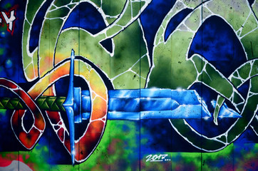 A fragment of detailed graffiti of a drawing made with aerosol paints on a wall of concrete tiles....