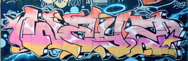 A fragment of detailed graffiti of a drawing made with aerosol paints on a wall of concrete tiles. Background image of street art in beige and pink color tones