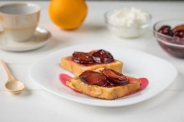 Toasted French bread, plum jam, cottage cheese and orange on a white wooden table.