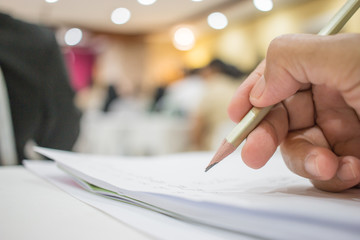 Business people making and writing notes at conference seminar with blur light business peple background.Seminar is form of academic instruction, offered by a commercial or professional organizatio