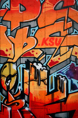A fragment of detailed graffiti of a drawing made with aerosol paints on a wall of concrete tiles. Background image of street art in warm red color tones