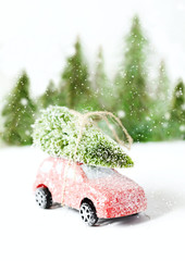 Christmas tree on red car toy with snow. Winter holiday celebration and Happy new year concept, copy space