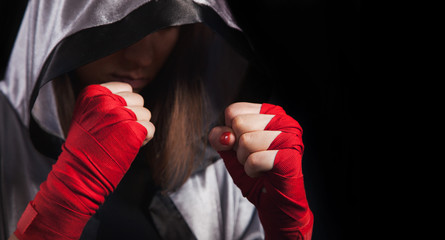 Female boxer makes a fight with a shadow, silver boxing robe and red boxing wraps, black background with copy space. Strong and confident, she will be a champion.