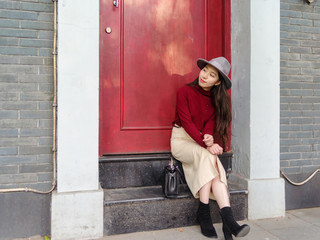 Beautiful Chinese sit on the step in front of a red door, waiting someone to go home.