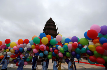 Students hold balloons at the Independence Monument while attending the celebration marking the 64th anniversary of the country's independence from France, in Phnom Penh