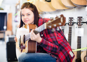 Teenage girl choosing acoustic guitar