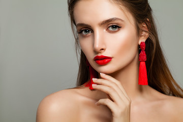 Young Woman with Red Lips Makeup and Jewelry Earrings. Beautiful Model, Cute Face