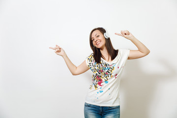 Beautiful emotional European young happy brown-haired woman with healthy clean skin and charming smile, dressed in casual light clothes, listens and enjoys music on headphones on a white background.