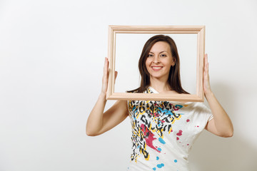 Portrait of a happy smiling brown-haired woman standing and holding empty wooden frame on the white background.