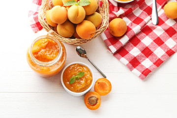 Apricot jam in bowl and glass jar on white wooden table