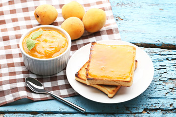 Apricot jam in bowl with bread toasts on blue wooden table