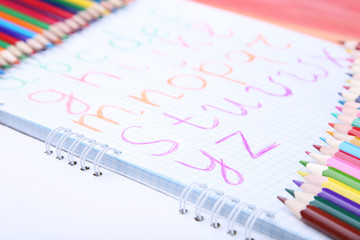 Handwritten alphabet in notebook with colorful pencils