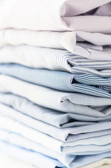 Neatly folded men's shirts of pastel tones. Close-up with soft focus