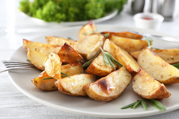 Plate with delicious rosemary potatoes on table