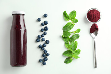 Composition with acai juice in glass bottle on light background