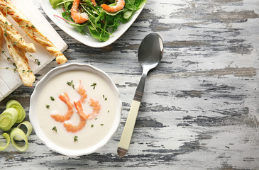 Tasty cream soup with fresh shrimps in bowl on table