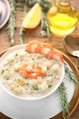 Tasty cream soup with fresh shrimps and croutons in bowl on table