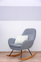 Grey rocking chair with pillow near light wall