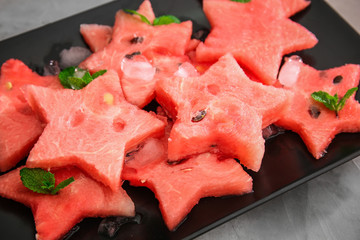 Plate with stars made of watermelon on grey background
