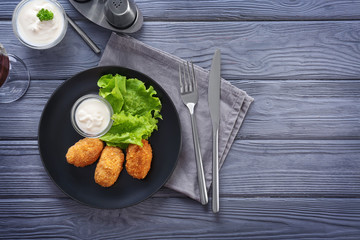 Plate with tasty salmon croquettes on table