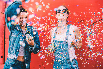 Hipster girlfriends celebrating with confetti