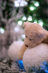 Beige teddy bear hugs snowballs with christmas tree and lights blurred in the background.
