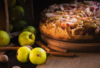 Homemade Apple pie on a round wooden board with green apples, cinnamon and red currants. Food concept. Low key image. An intimate, homely atmosphere. A beam of light on the cake and apples