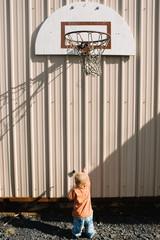 Boy playing under basketball hoop