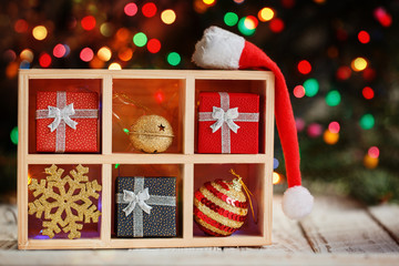 Wooden box filled with Christmas, decorations, present, box, gold snowflake and ball with Santa hat on colorful bokeh background.