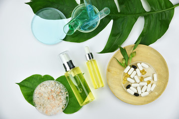 Cosmetic bottle containers with green herbal leaves, Blank label for branding mock-up, Natural beauty product concept.