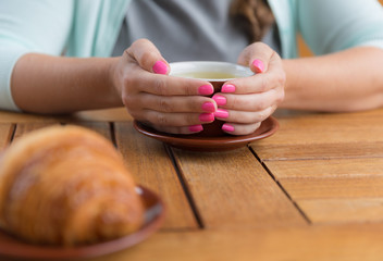Young woman with pink manicure holding a cup of green tea, no face
