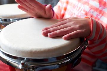 Children's hands on the drum