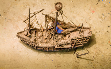 Old wooden boat model on the table.