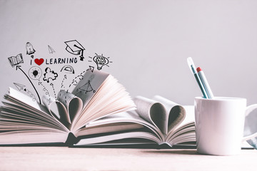 A cup of coffee and open books with i love learning doodles
