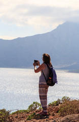 A young woman, a European tourist with a backpack, stands on the edge of a cliff above the sea and photographs a smartphone landscape