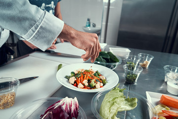 The chef prepares the dish. Sprinkle the salad with spices. Cooking. Professional kitchen. Salad dressing. Spices for salad