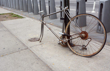 Broken, rusty bicycle locked to a metal pole