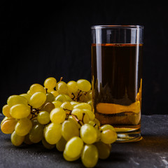 Image of glass with juice, bunch of grapes on stone board