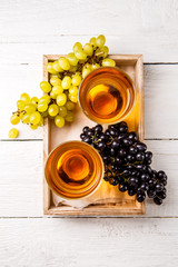 Photo on top of wooden box with two glasses of wine, black and green grapes