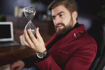 Businessman playing hourglass at his office