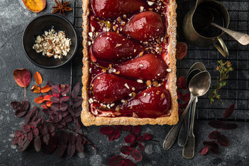 tart with red wine poached pears served with nuts. top view