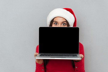 Close-up photo of happy caucasian woman in Santa's hat hiding behind blank screen laptop