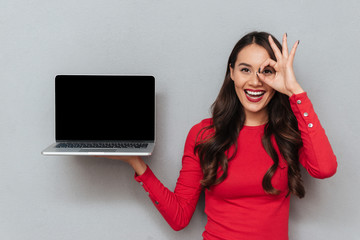 Close-up portrait of happy attractive woman showing empty laptop display, looking looking through OK gesture