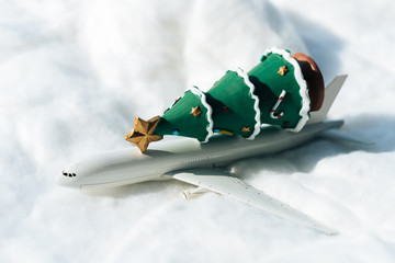 Miniature figure: white airplane carrying Christmas tree on white snow. Christmas Holiday decorative concept.