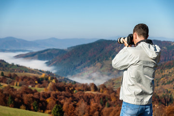 Photographer and traveler taking picture in mountains